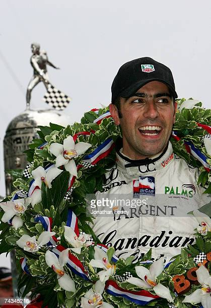 Dario Franchitti driver of the Canadian Club Andretti Green Racing Dallara Honda celebrates in victory lane next to the Borg Warner Trophy after...