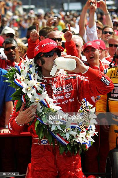 Dario Franchitti of Scotland driver of the Target Chip Ganassi Racing Dallara Honda drinks the ceremonial winner's milk over in victory lane in...