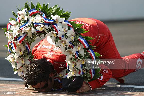 Dario Franchitti of Scotland driver of the Target Chip Ganassi Racing Dallara Honda kisses the yard of bricks on the front stretch after winning the...