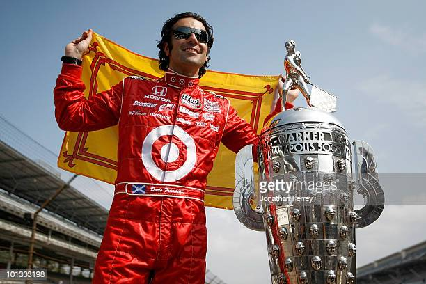 Dario Franchitti of Scotland driver of the Target Chip Ganassi Racing Dallara Honda poses with Borg Warner Trophy on the yard of bricks during the...
