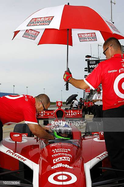 Dario Franchitti of Scotland driver of the Target Chip Ganassi Racing Dallara Honda sits in his car as his crew work on the car during practice for...