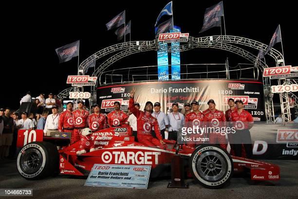 Dario Franchitti of Scotland driver of the Target Chip Ganassi Racing Dallara Honda celebrates winning the IndyCar Championship with his team during...