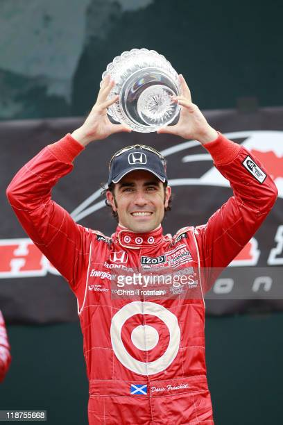 Dario Franchitti of Scotland driver of the Target Chip Ganassi Racing Dallara Honda lifts the trophy following his victory in the IZOD IndyCar Series...