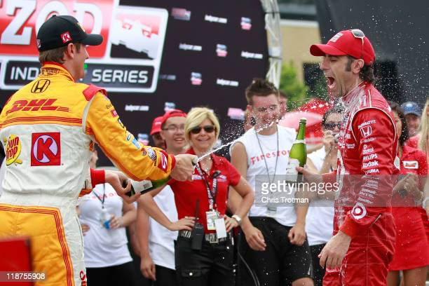Dario Franchitti of Scotland driver of the Target Chip Ganassi Racing Dallara Honda is sprayed with champagne by third place finisher Ryan HunterReay...