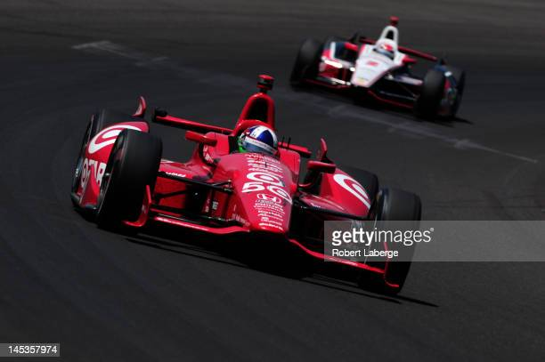 Dario Franchitti of Scotland driver of the Target Chip Ganassi Racing Honda leads Ryan Briscoe of New Zealand driver of the IZOD Team Penske...