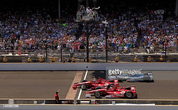 Dario Franchitti of Scotland driver of the Target Chip Ganassi Racing Honda crosses the yard of bricks start/finish line to take the checkered flag...