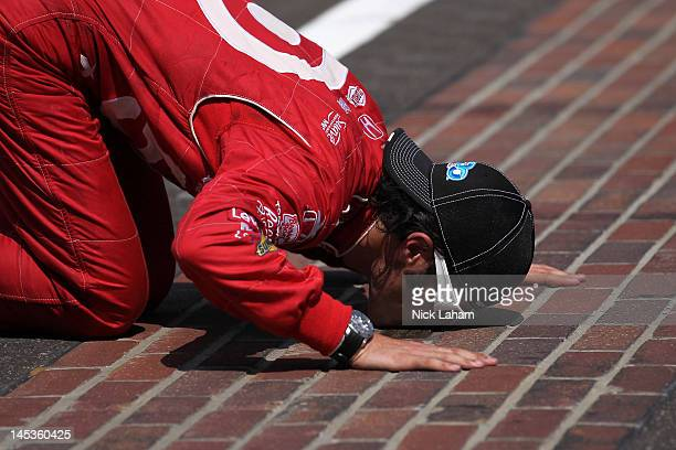Dario Franchitti of Scotland driver of the Target Chip Ganassi Racing Honda kisses the yard of bricks in celebration of winning the IZOD IndyCar...