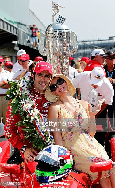 Dario Franchitti of Scotland driver of the Target Chip Ganassi Racing Honda pose for a photo in victory lane in front of the BorgWarner trophy after...