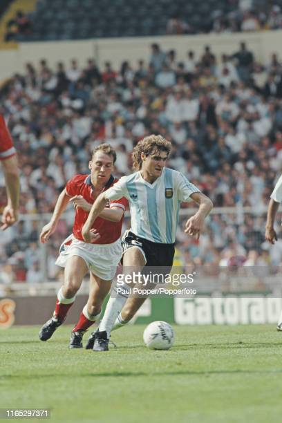 Dario Franco of Argentina pictured making a run with the ball as David Platt of England chases during play between England and Argentina in the 1991...