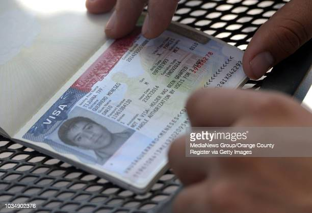 Dario GuerreroMeneses looks over his temporary VISA as he talks about his immigration ordeal at his home in Carson CA on Wednesday October 22 2014...