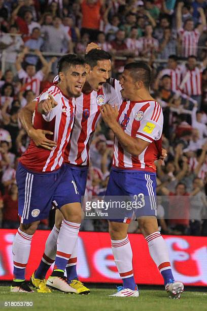Dario Lezcano of Paraguay celebrates with teammates Roque Santa Cruz and Richard Ortiz after scoring the first goal of his team during a match...