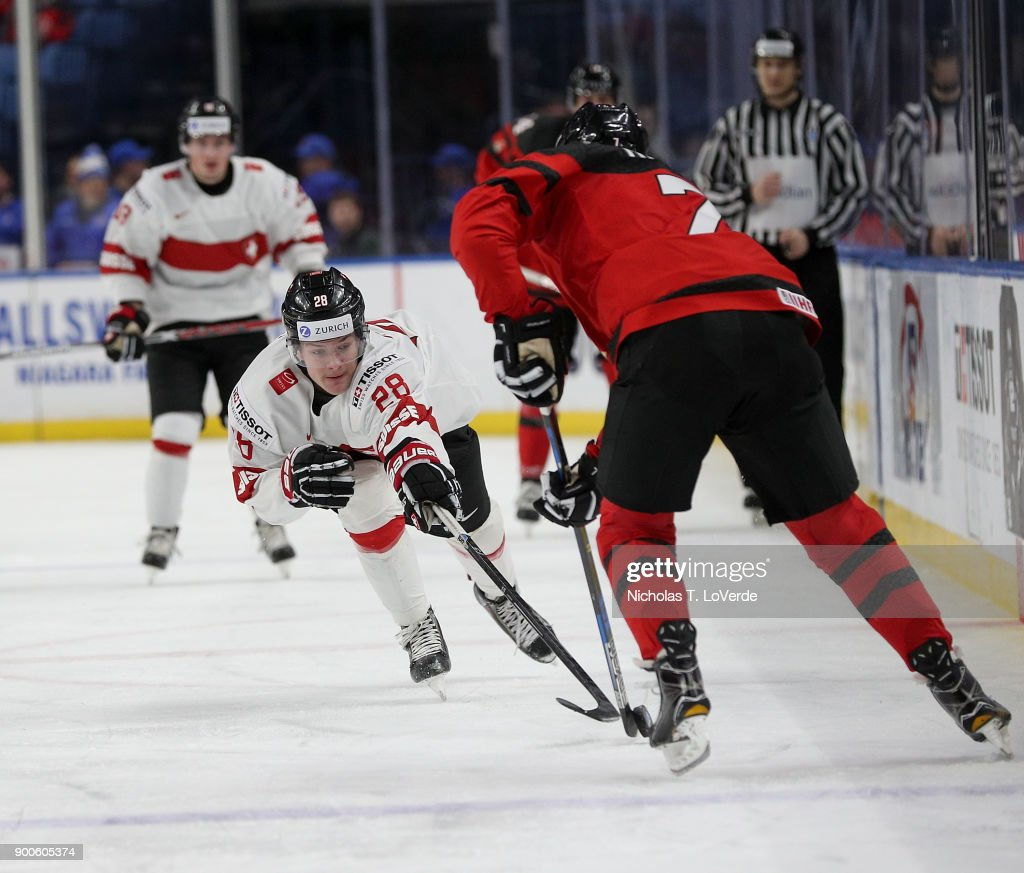 Dario Rohrbach #28 of Switzerland tries to poke the puck free from Cale Makar #7 of Canada during the second period of play in the Quarterfinal IIHF World Junior Championship game at the KeyBank Center on January 2, 2018 in Buffalo, New York.