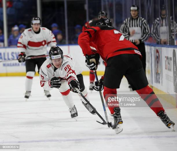 Dario Rohrbach of Switzerland tries to poke the puck free from Cale Makar of Canada during the second period of play in the Quarterfinal IIHF World...