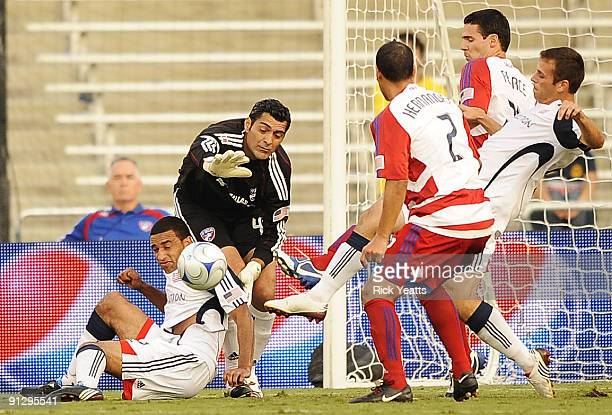 Dario Sala of the FC Dallas tries to make a save with pressure from Amaechi Igwe of the New England Revolution as Chris Tierney of the New England...