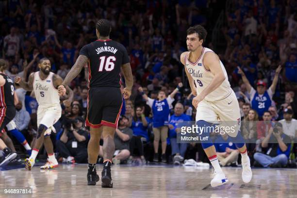 Dario Saric and Amir Johnson of the Philadelphia 76ers react in front of James Johnson of the Miami Heat after a made three point basket by Dario...
