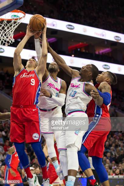 Dario Saric and Richaun Holmes of the Philadelphia 76ers go up for a rebound against Dwyane Wade and Bam Adebayo of the Miami Heat in the second...