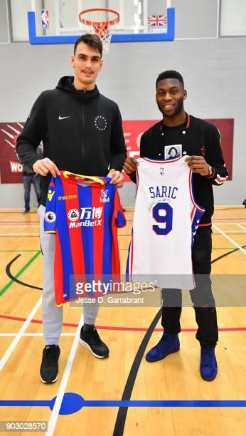 Dario Saric of the Philadelphia 76ers and Jeffrey Schlupp of Crystal Palace football team poses for a photo with a Crystal Palace football player...
