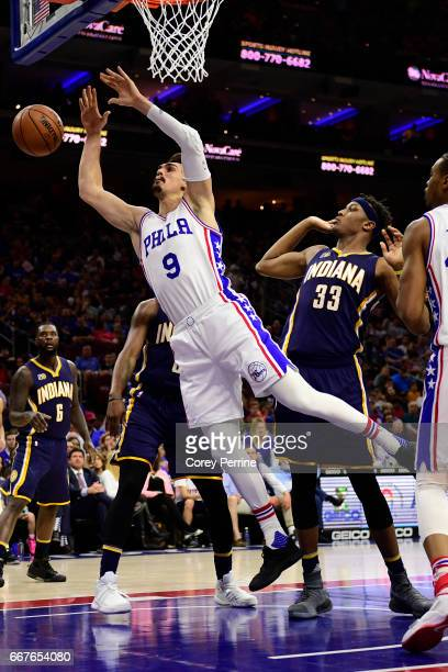 Dario Saric of the Philadelphia 76ers is fouled by Myles Turner of the Indiana Pacers during the second quarter at the Wells Fargo Center on April 10...
