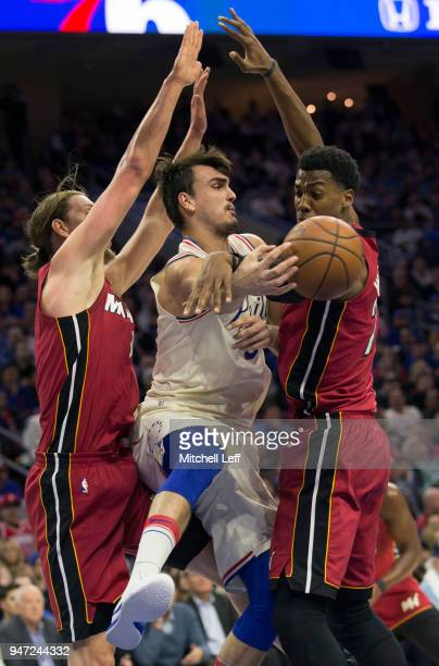 Dario Saric of the Philadelphia 76ers passes the ball around Kelly Olynyk and Hassan Whiteside of the Miami Heat in the second quarter during Game...