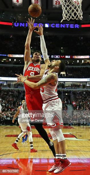Dario Saric of the Philadelphia 76ers shoots over Denzel Valentine of the Chicago Bulls at the United Center on March 24 2017 in Chicago Illinois The...