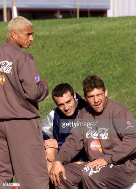 Dario Silva Paolo Montero and Fabian O'Neil watch other players during soccer practice 27 May 2000 in Montevideo Uruguay Los jugadores de la...