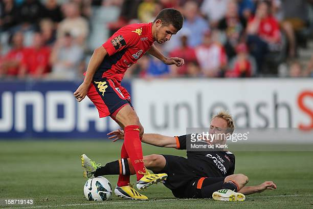 Dario Vidosic of Adelaide is tackled by Mitchell Nichols of Brisbane during the round 13 ALeague match between Adelaide United and the Brisbane Roar...