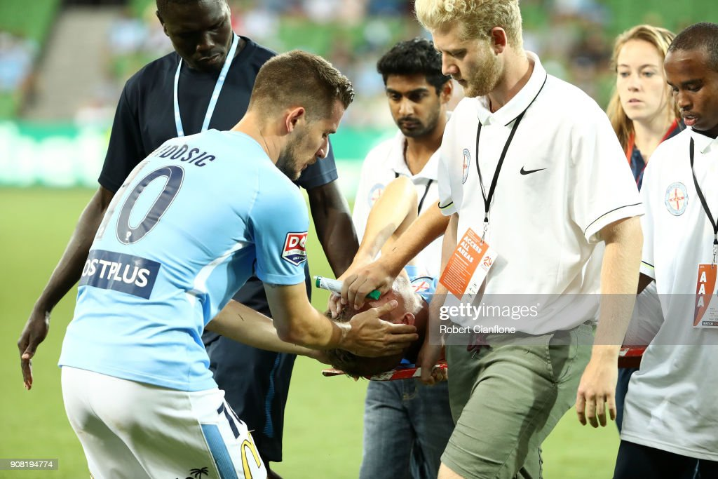 Dario Vidosic of the City consoles Nathaniel Atkinson as he is stretchered off with an injury during the round 17 A-League match between Melbourne City and Adelaide United at AAMI Park on January 21, 2018 in Melbourne, Australia.