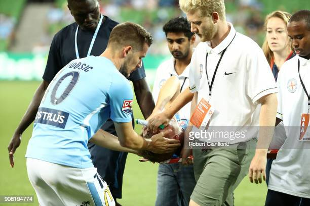 Dario Vidosic of the City consoles Nathaniel Atkinson as he is stretchered off with an injury during the round 17 ALeague match between Melbourne...