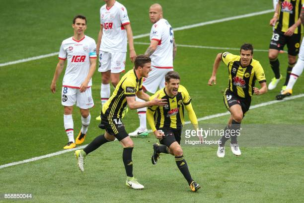 Dario Vidosic of the Phoenix celebrates with teammates Alex Rufer and Andrija Kaludjerovic after scoring a goal during the round one ALeague match...