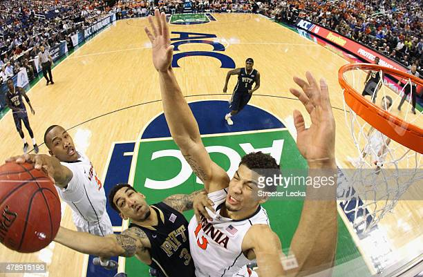 Darion Atkins and teammate Anthony Gill of the Virginia Cavaliers try to stop Cameron Wright of the Pittsburgh Panthers during the semifinals of the...
