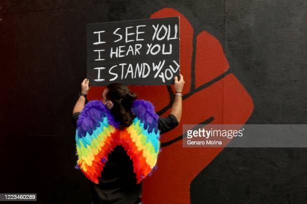 HOLLYWOOD CA JUNE 14 2020 Darius Ardalan stands near a red fist while joining thousands who participate in the All Black Lives Matter solidarity...