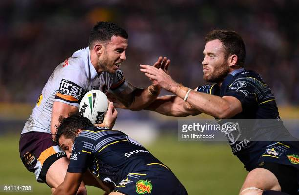 Darius Boyd of the Broncos is tackled by Gavin Cooper and Te Maire Martin of the Cowboys during the round 26 NRL match between the North Queensland...