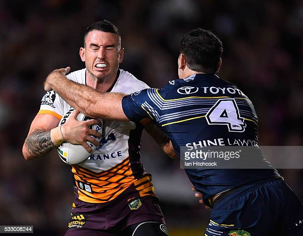 Darius Boyd of the Broncos is tackled by Kane Linnett of the Cowboys during the round 11 NRL match between the North Queensland Cowboys and the...