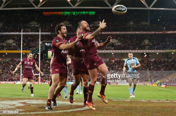 Darius Boyd of the Maroons celebrates scoring a try with team mates during game three of the State of Origin series between the Queensland Maroons...
