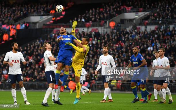 Darius Charles of AFC Wimbledon and Michel Vorm of Tottenham Hotspur battle for the ball during The Emirates FA Cup Third Round match between...