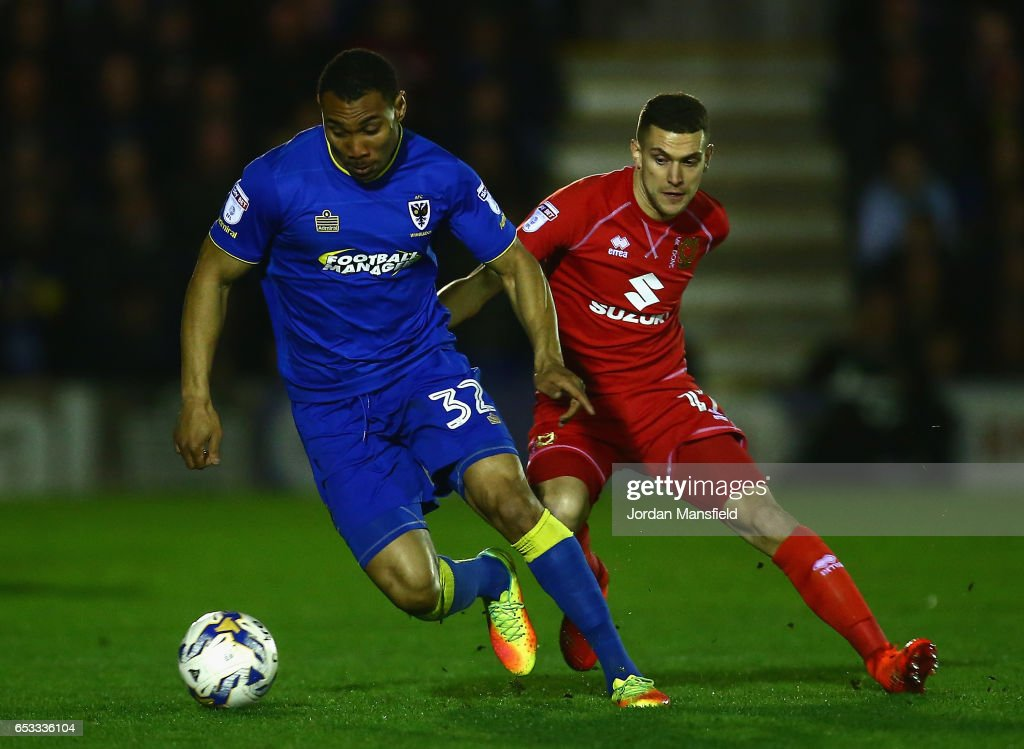 Darius Charles of A.F.C. Wimbledon is challenged by George Williams of Milton Keynes Dons during the Sky Bet League One match between A.F.C. Wimbledon and Milton Keynes Dons at The Cherry Red Records Stadium on March 14, 2017 in Kingston upon Thames, England.