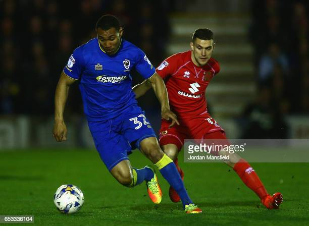 Darius Charles of AFC Wimbledon is challenged by George Williams of Milton Keynes Dons during the Sky Bet League One match between AFC Wimbledon and...