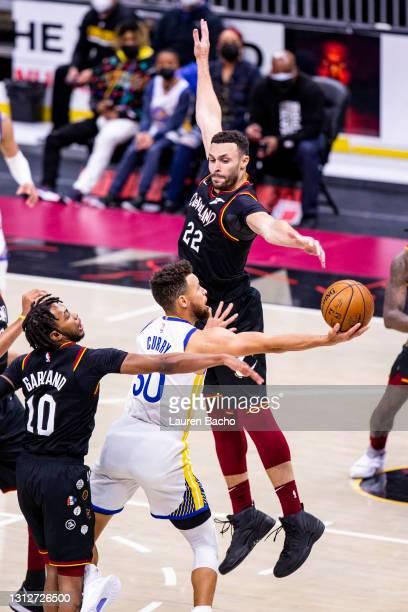 Darius Garland and Larry Nance Jr. #22 of the Cleveland Cavaliers attempt to block a shot attempt by Stephen Curry of the Golden State Warriors...