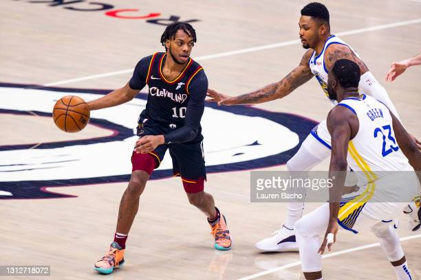 Darius Garland of the Cleveland Cavaliers handles the ball against Kent Bazemore and Draymond Green of the Golden State Warriors in the first half at...
