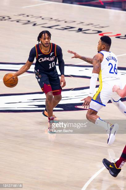 Darius Garland of the Cleveland Cavaliers passes the ball against Kent Bazemore of the Golden State Warriors at Rocket Mortgage Fieldhouse on April...