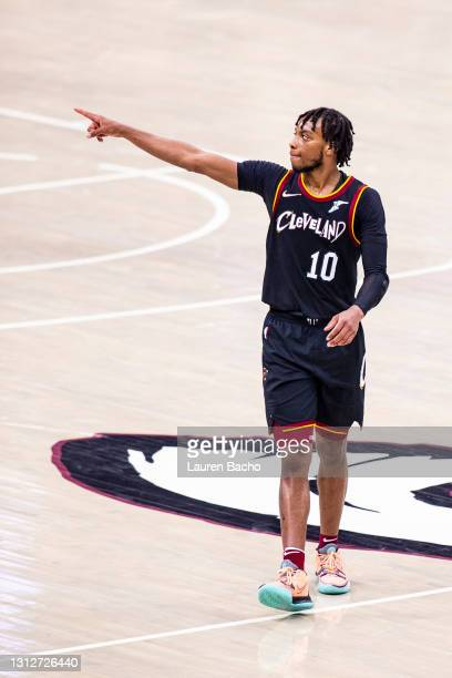 Darius Garland of the Cleveland Cavaliers points at Larry Nance Jr. #22 of the Cleveland Cavaliers after Nance made a three point shot during the...