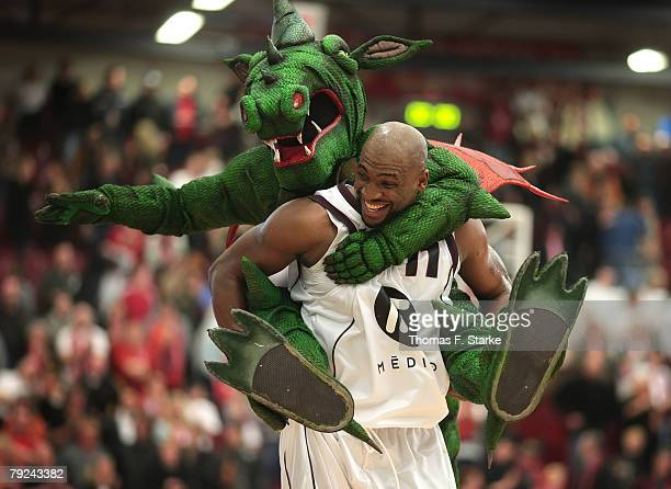 Darius Hall of Quakenbrueck celebrates with the mascot after the Bundesliga game between Artland Dragons Quakenbrueck and Giessen 46ers at the...
