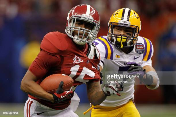 Darius Hanks of the Alabama Crimson Tide runs as Tyrann Mathieu of the Louisiana State University Tigers pulls his jersey from behind during the 2012...