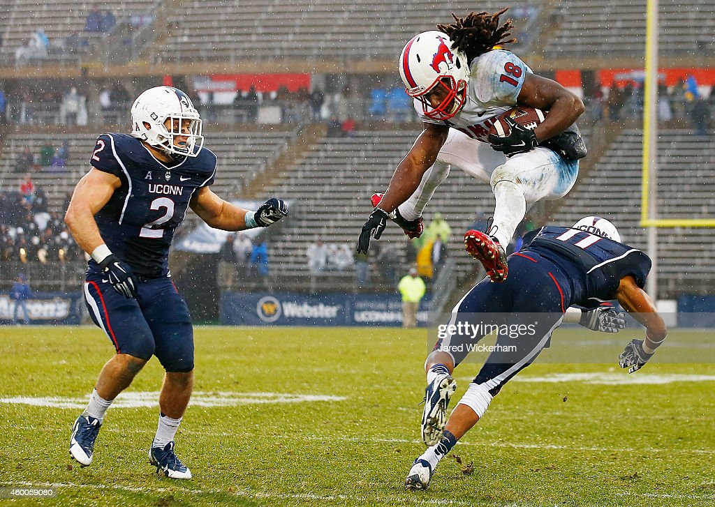 Darius Joseph #18 of the SMU Mustangs hurdles Javon Hadley #11 of the Connecticut Huskies in front of his teammate, Graham Stewart #2 in the second half after catching a pass during the game at Rentschler Field on December 6, 2014 in East Hartford, Connecticut.