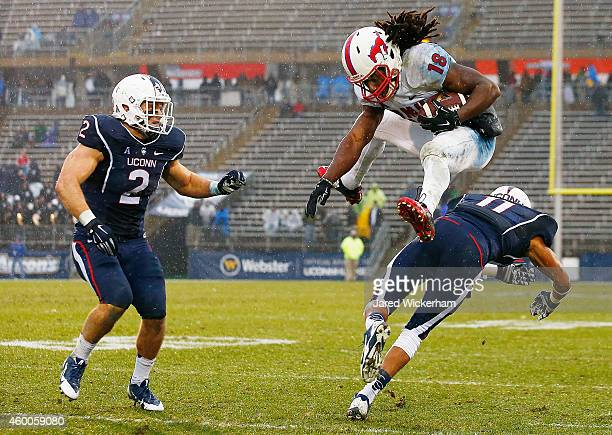 Darius Joseph of the SMU Mustangs hurdles Javon Hadley of the Connecticut Huskies in front of his teammate Graham Stewart in the second half after...