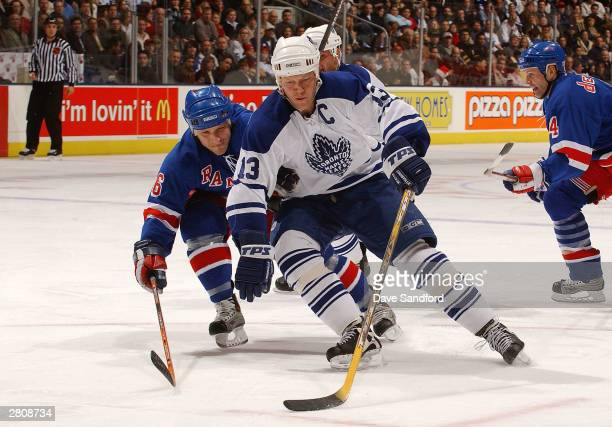 Darius Kasparaitis of the New York Rangers tries to stop Mats Sundin of the Toronto Maple Leafs as he drives to the net with the puck during the game...