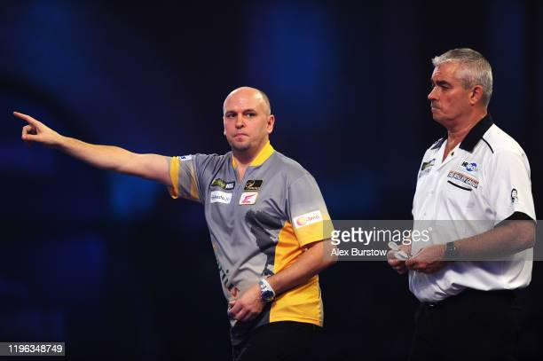 Darius Labanauskas of Lithuania celebrates as his opponent Steve Beaton of England looks on in their Fourth Round match during Day Thirteen of the...