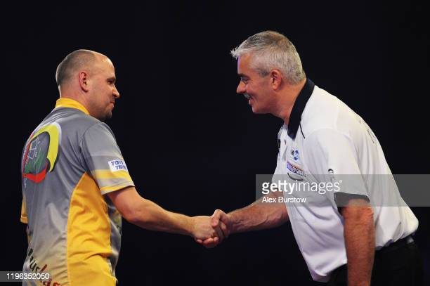 Darius Labanauskas of Lithuania shakes hands with Steve Beaton of England after their Fourth Round match during Day Thirteen of the 2020 William Hill...