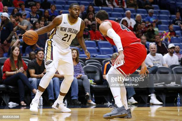Darius Miller of the New Orleans Pelicans drives against Nikola Mirotic of the Chicago Bulls during a preseason game at the Smoothie King Center on...