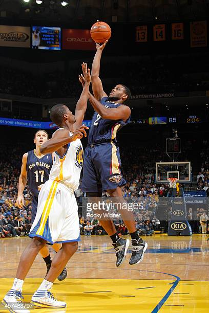 Darius Miller of the New Orleans Pelicans shoots against Harrison Barnes of the Golden State Warriors on December 17 2013 at Oracle Arena in Oakland...
